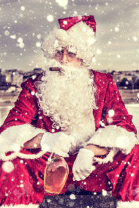 Sad Santa Claus with cigar and bottle of brandy